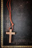 Closeup of simple wooden Christian cross necklace on holy Bible with copy space