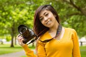Portrait of beautiful female photographer standing at the park