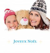 Mother and daughter holding teddy bear against Christmas greeting card
