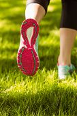 Woman in running shoes jogging on grass in the park