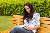 Happy brunette reading a book on a bench in the park