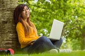 Side view portrait of relaxed young woman using laptop in the park