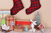 Hand-made Christmas gifts and decorations on fireplace in room