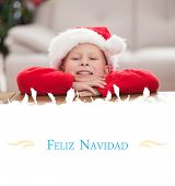 Festive little boy smiling at camera against Christmas greeting card