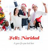 Business team punching the air to celebrate christmas against feliz navidad