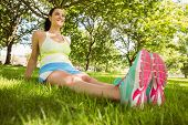 Happy brunette in sportswear relaxing on the grass in the park
