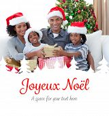 Smiling family sharing Christmas presents against joyeux noel