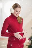 Pregnant woman making a heart with her hands on her belly against twinkling stars