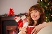 Smiling redhead holding a mug of hot drink at christmas at home in the living room