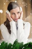 Pretty brunette with ear muffs thinking against green fir branches with snow