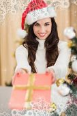 Surprised brunette showing a gift against snowflake frame