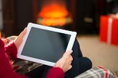 Woman in jumper using tablet at christmas at home in the living room