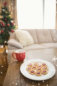 Cookies and mug on coffee table at christmas against snow falling