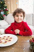 Festive little boy having milk and cookies against snow falling
