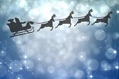 Silhouette of santa claus and reindeer against shimmering light design on blue