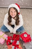 Festive little girl smiling at camera with gifts against twinkling stars