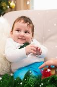 Cute baby boy on the couch at christmas against green fir branches with snow