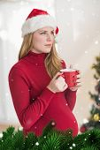 Festive pregnant woman holding mug while standing against green fir branches with snow