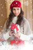 Smiling brunette holding gift and shopping bags against snow falling