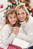 Festive mother and daughter beside christmas tree against snow falling