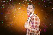 Geeky hipster pointing at camera against colourful fireworks exploding on black background