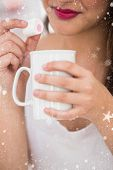 Close up of woman holding mug and marshmallow against snow falling