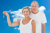 Mature couple smiling at camera with new house key against cloudy sky