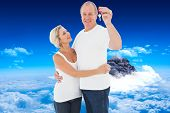 Mature couple smiling at camera with new house key against mountain peak through clouds
