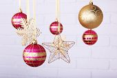 Christmas balls and snowflakes hanging on light blurred background