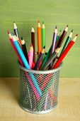 Colorful pencils in metal holder on wooden table and green wooden background