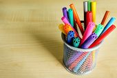 Colorful markers in metal holder on wooden background