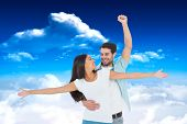 Happy casual couple cheering together against bright blue sky with clouds
