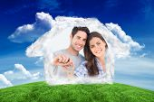 Man and wife holding a key with a house keychain against green field under blue sky