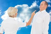 Angry older couple arguing with each other against cloudy sky
