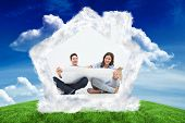 Man and his wife looking at their house plans against green field under blue sky