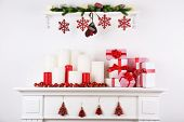 Christmas decorations with candles on mantelshelf on white background