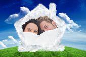 Couple hiding under the duvet against green field under blue sky