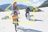 Carefree couple going on a bike ride on the beach against house outline