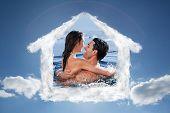 Joyful couple cuddling each other against cloudy sky with sunshine