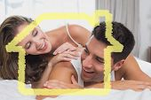 Romantic young couple in bed at home against house outline