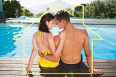 Couple sitting by swimming pool on a sunny day against house outline