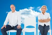 Upset couple not talking to each other after fight against cloudy sky