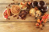 Chocolate cookies with bowl of cocoa, nuts, coffee beans, slice of citrus and cinnamon on rustic background