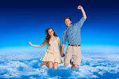 Cheerful young couple jumping against blue sky over clouds at high altitude
