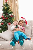 Cute boy and baby brother on couch at christmas against snow falling