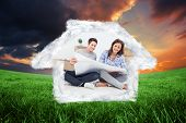 Man and woman looking at their house plans against green field under orange sky