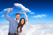 Happy young couple cheering against bright blue sky with clouds