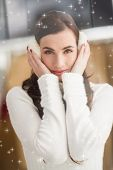 Pretty brunette with ear muffs against twinkling stars