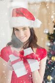 Beauty brunette showing gift at christmas against snow falling