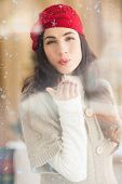 Pretty brunette blowing a kiss against snow falling